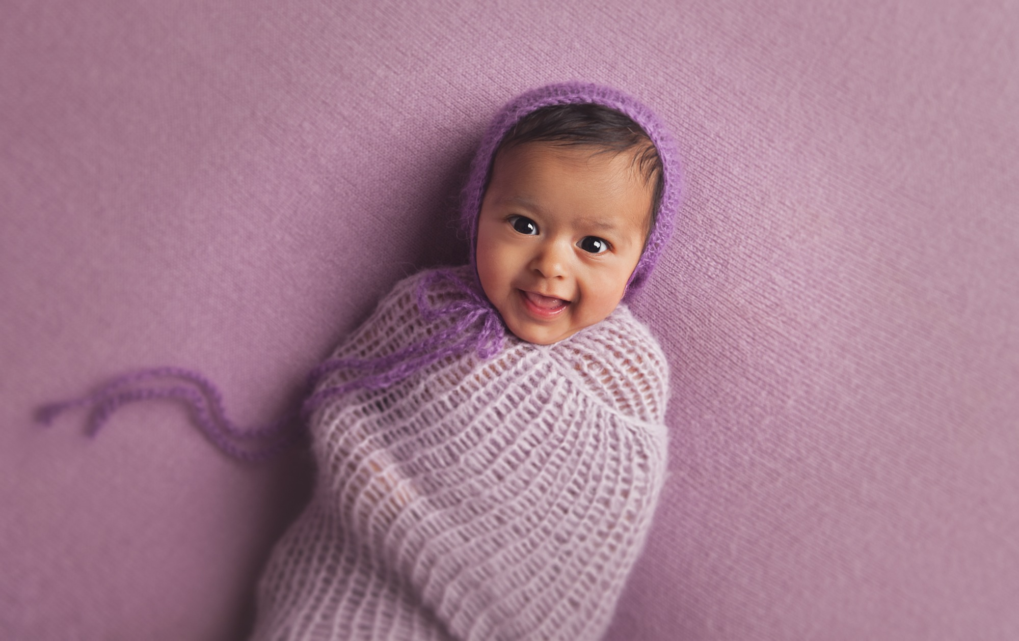 Newborn girl in purple swaddle setup