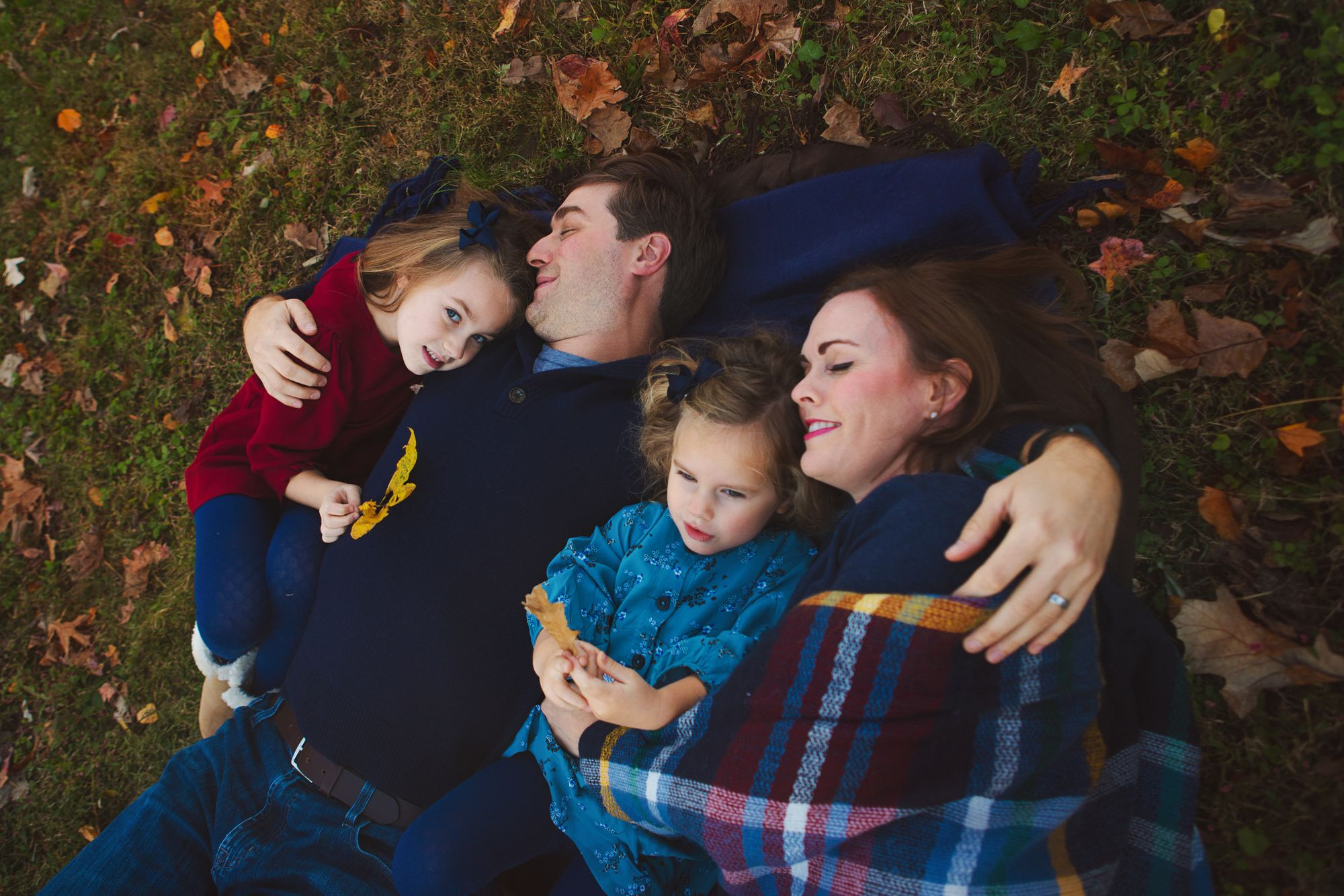Family posing on grass during an outdoor photo shoot