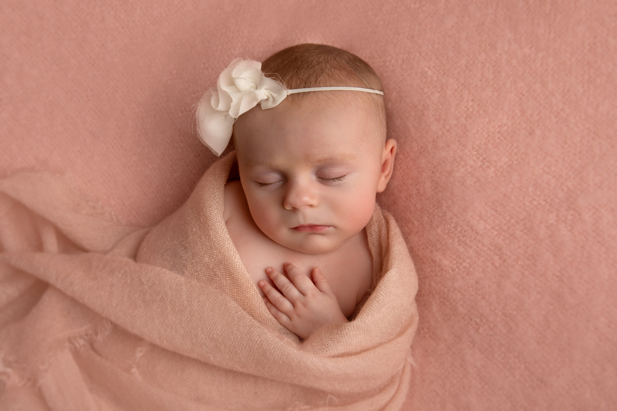 Newborn with white headband in studio photoshoot