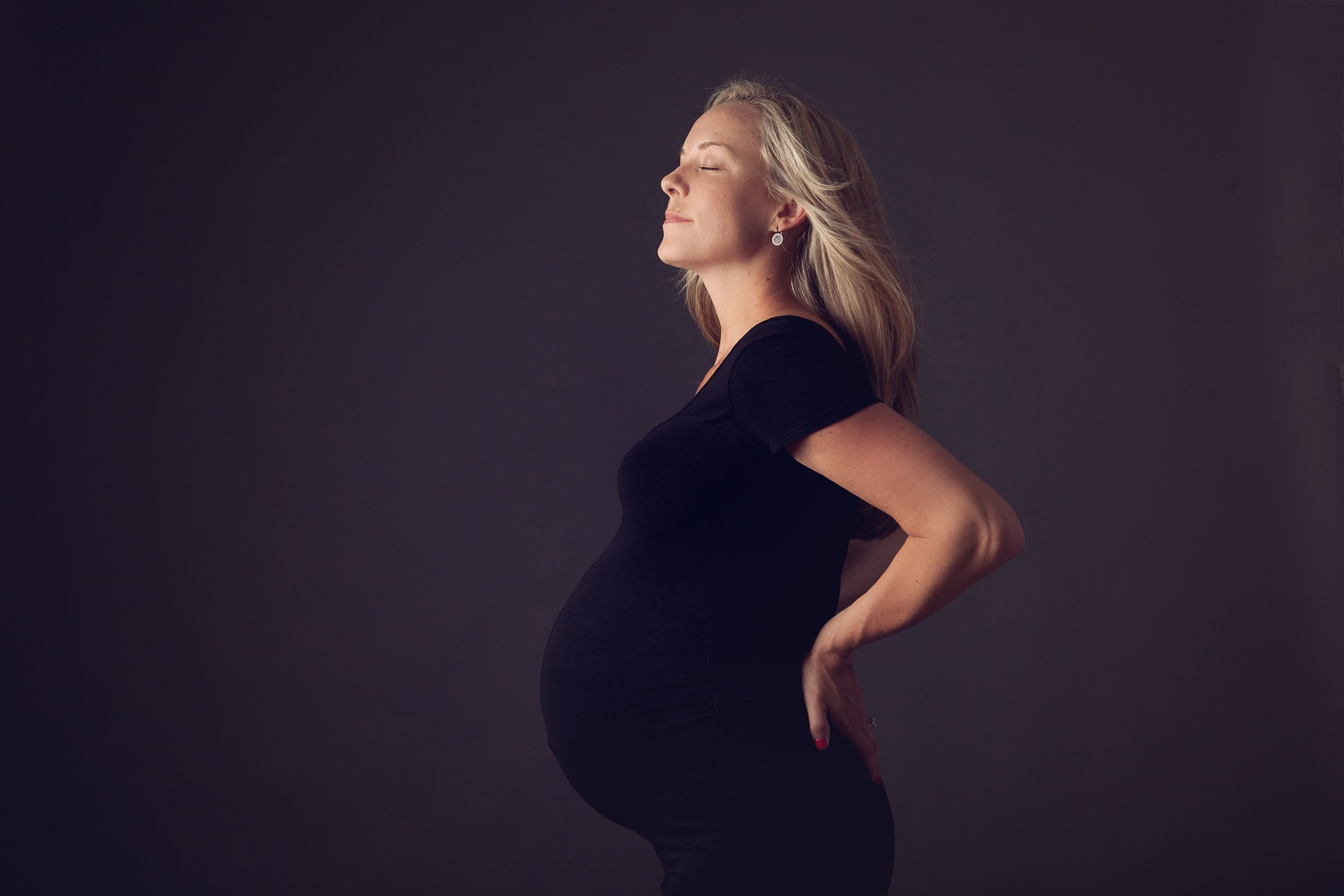 Maternity portrait studio session of a mother in a black dress