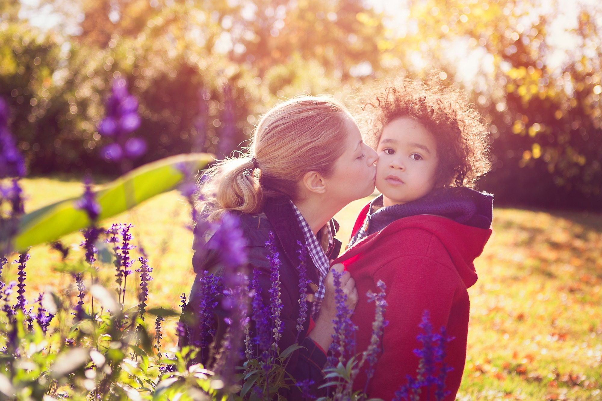 Portrait photo of a mother kissing her son in a garden
