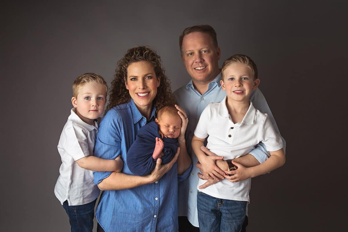 Portrait of family in blue clothes - parents, siblings, newborn