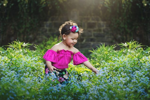 Baby girl in blue flower field
