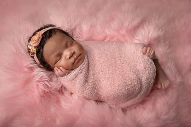 Baby girl swaddled in pink