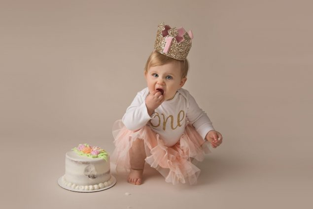 Milestone session with a baby girl eating a cake