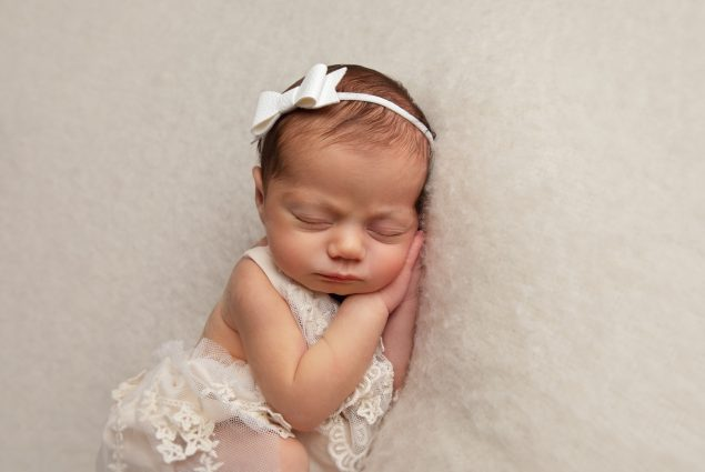 Newborn baby girl sleeping on white blanket
