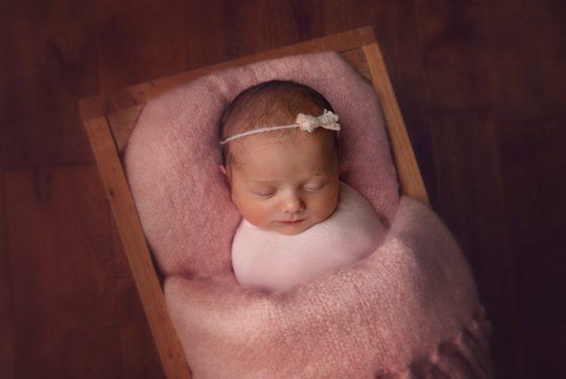 Newborn girl sleeping in pink prop crate