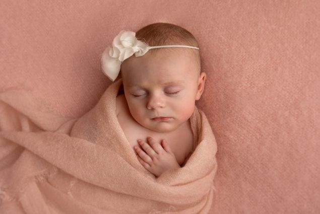 Newborn with white headband in studio photoshoot