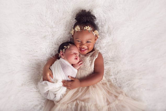 Baby and newborn hugging in studio session in Baltimore
