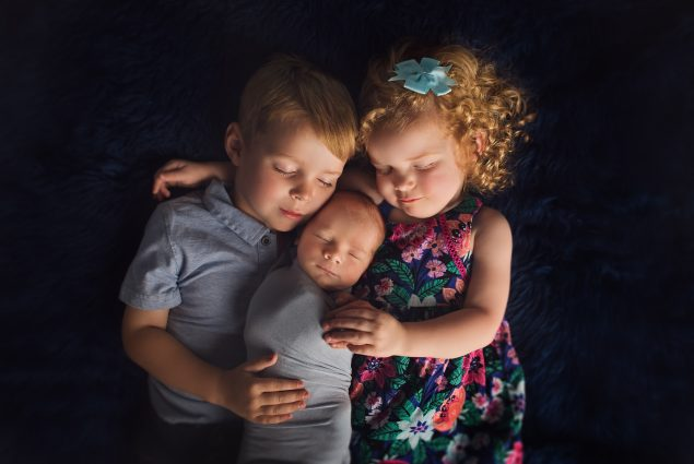 Boy and girl toddlers with newborn