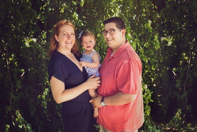 Family of three posing under a tree
