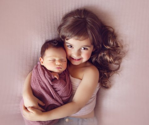 Little girl hugging swaddled newborn on pink background