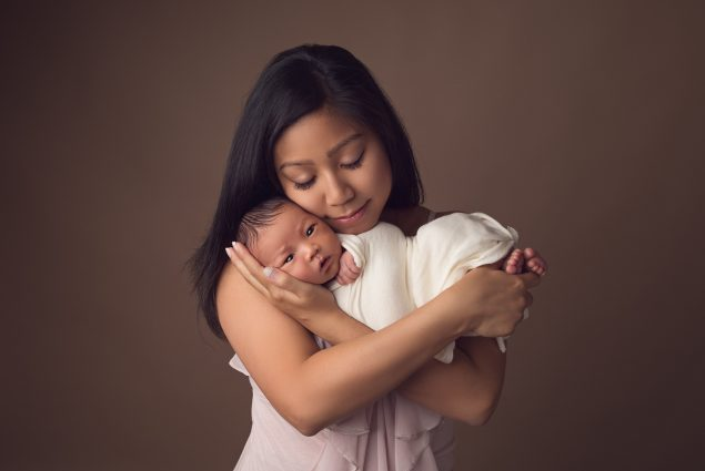 Mom holding her newborn during a photoshoot in studio