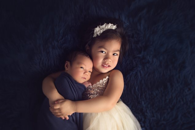 Newborn and toddler portrait on a blue blanket