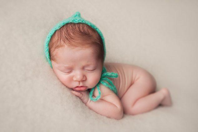 Newborn baby boy with green hat sleeping on beige blanket