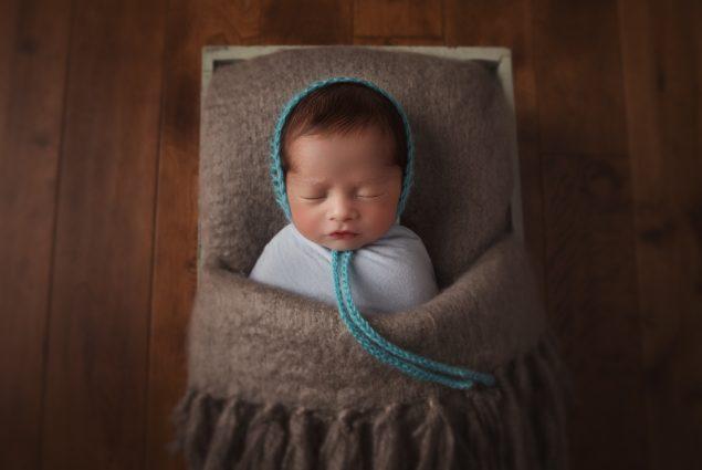 Newborn sleeping in a crate