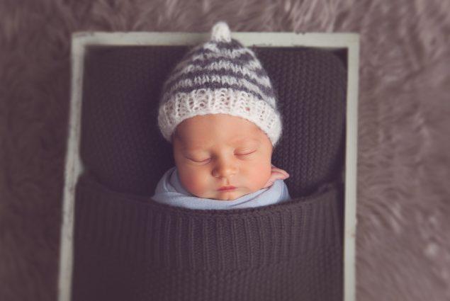 Newborn sleeping in prop crate