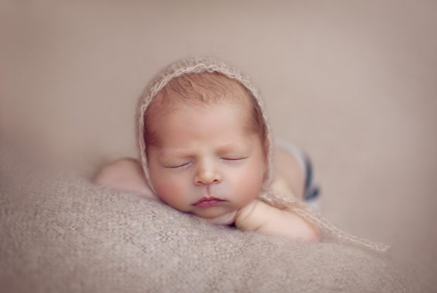 Newborn with a hat sleeping on beige blanket
