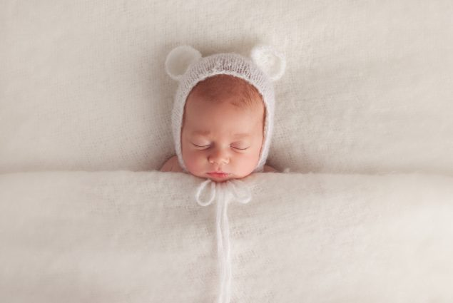 Newborn sleeping under white blanket