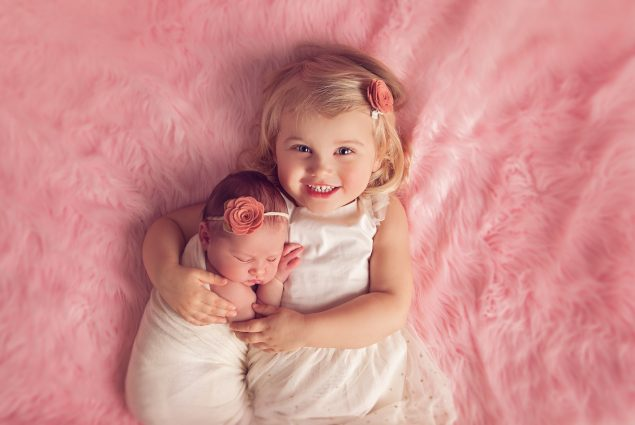 Portrait of a two-year-old with baby on pink blanket