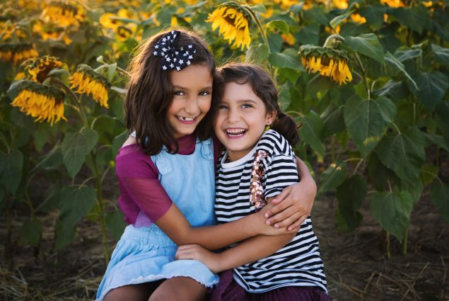 Portrait of two girls in a sunflower field