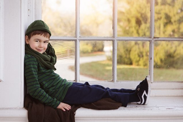 Professional portrait of boy sitting in the window
