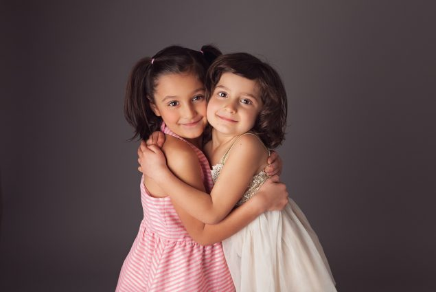 Sisters hugging in studio portrait