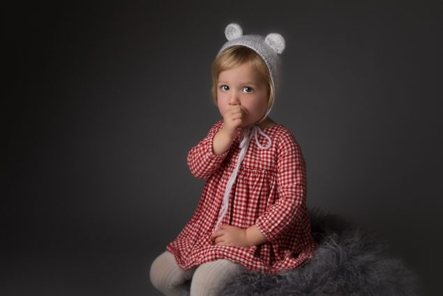 Studio portrait of a toddler girl sucking her thumb
