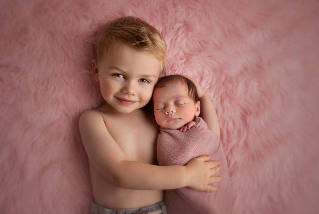 Toddler hugging swaddled newborn on pink blanket